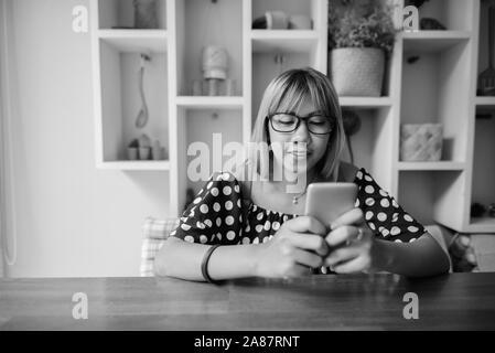 Young Asian teenage girl using phone at home en noir et blanc Banque D'Images