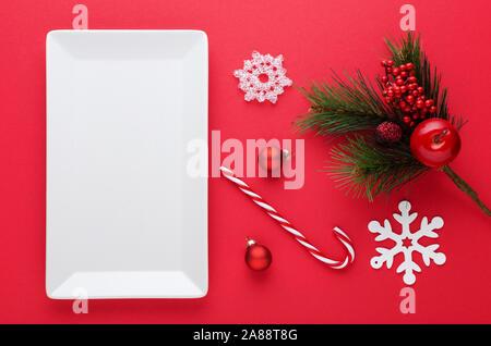 Décoration de table de Noël avec une plaque blanche, babioles, flocons et canne de Noël sur rouge Banque D'Images