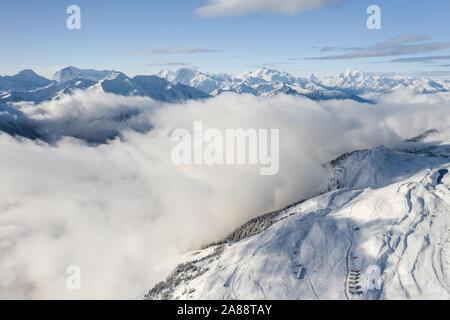 Vue aérienne d'une forêt couverte de neige fraîche et nuages dans le domaine d'Aletsch Arena. La Suisse à l'automne