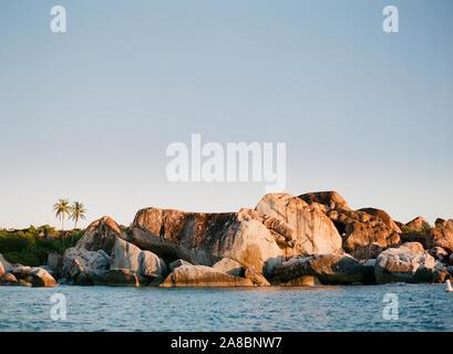 Au coucher du soleil sur le rocher rochers au les bains plage avec des palmiers à l'arrière-plan, l'île de Virgin Gorda, Îles Vierges Britanniques Banque D'Images