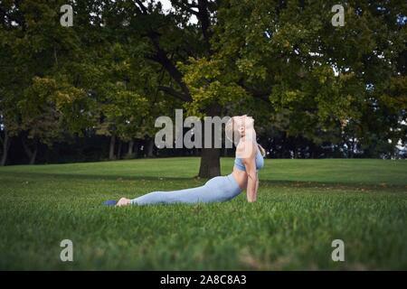 Young woman doing yoga dans le parc, la gymnastique, l'Olympiapark, Munich, Allemagne