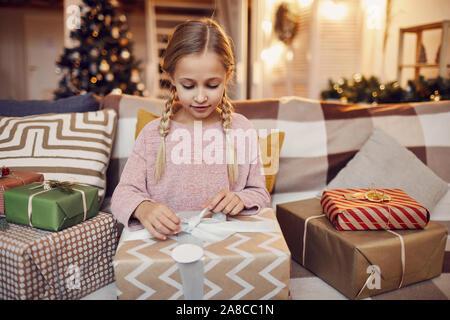 Petite fille assise sur le canapé et l'ouverture de gros cadeau de Noël qu'elle l'obtenant de Père Noël pour Noël à la maison