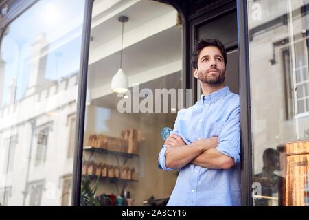 Portrait de propriétaire de sexe masculin se tient en dehors de Coffee Shop Banque D'Images
