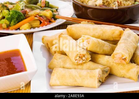 Rouleaux de printemps crevettes sautés asiatiques servis avec riz frit au poulet et aux légumes. Une sauce au goût sucré est inclus. Tourné en lumière naturelle Banque D'Images