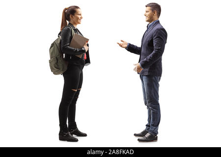 Profil de pleine longueur tourné d'une étudiante ayant une conversation avec un jeune homme isolé sur fond blanc Banque D'Images