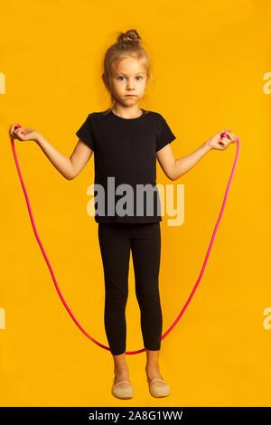 Petite fille pleine longueur en sautant sur un justaucorps noir corde rose impression contre fond jaune. Banque D'Images