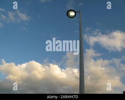 Lampadaire contre fond bleu du ciel et nuages blancs Banque D'Images