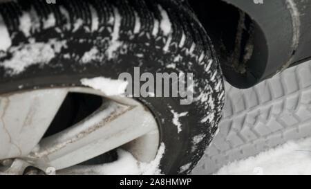 Close up d'un des pneus de voitures sur une route enneigée. Close-up de roues de voiture pneus en caoutchouc en profonde neige de l'hiver. Banque D'Images