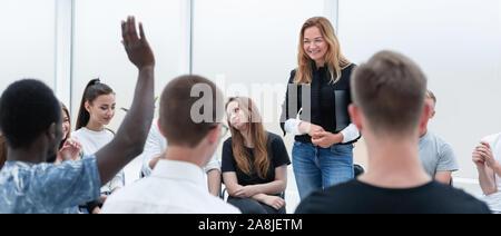 Jeune femme debout dans un cercle de ses collègues.
