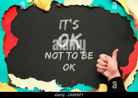 Texte 'c'est bon de ne pas être OK ' en papier brûlé cadre sur fond noir et part montrant OK signe. Citation positive pour les personnes souffrant de personnalité Banque D'Images