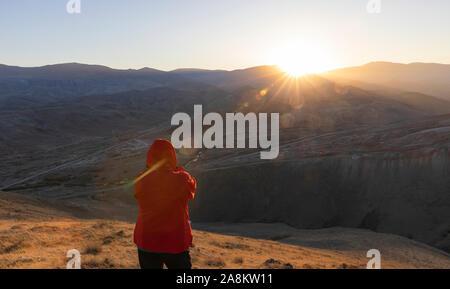 Randonneur regardant le coucher du soleil dans les montagnes Banque D'Images