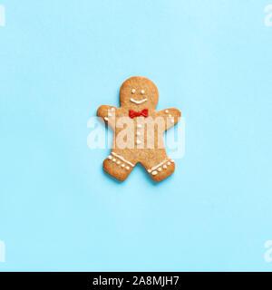 Gingerbread Man sur fond bleu. Noël à la mode composition minimale - homemade gingerbread man cookie, vue de dessus, copiez l'espace. Banque D'Images
