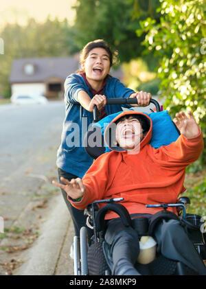 Teen girl running et souriant tout en poussant mobilité petit garçon dans un fauteuil roulant à l'extérieur