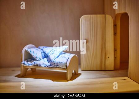 Meubles de poupée lit avec des couvertures et oreillers dans la dollhouse. Miniature. Banque D'Images