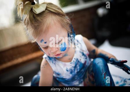 Un adorable petit bambin, fille a du plaisir à jouer avec les peintures de coloriage, obtenir malpropre et ayant beaucoup de plaisir, tourné dans un environnement d'accueil Banque D'Images
