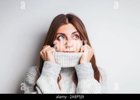 Femme dans un pull en laine confortable avec un sourire amical à côté Banque D'Images