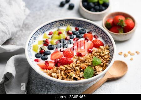 Bol de petit-déjeuner avec du yogourt, céréales, baies et fruits. Blueberry, graines de grenade, kiwi, fraise et crunchy granola avoine. L'alimentation saine Banque D'Images