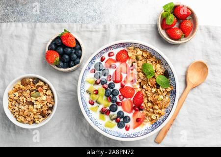 Petit-déjeuner sain bol de yogourt aux fruits rouges de bleuet, fraise, kiwi, pomme grenade et granola sur lin texture. Vue d'en haut. Concept de l'alimentation propre, d Banque D'Images