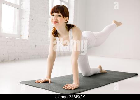Exercices de poids corporel - fitness femme jambes poteaux incendie pots-de-vin. Fille active les muscles fessiers formation sensibilisation une jambe sur le côté et le dos pour