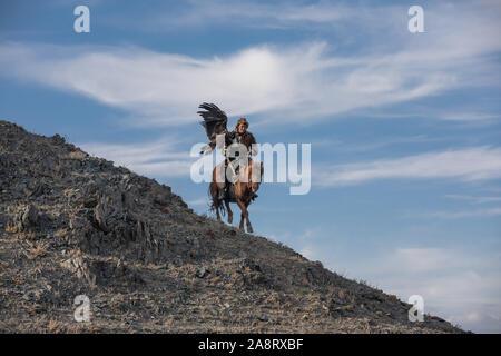 Kazakh traditionnel eagle hunter en ordre décroissant d'une colline à cheval tout en portant son aigle doré. Ulgii, la Mongolie. Banque D'Images