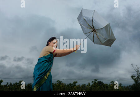 Femme essayant de tenir sur le parapluie en cas de mauvais temps Banque D'Images