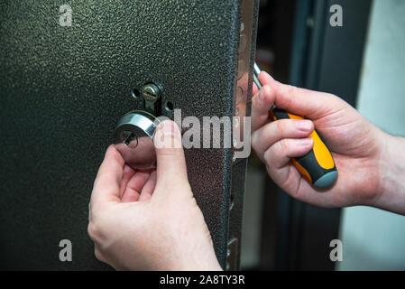 Un homme répare une serrure de porte. Close-up. focus sélectif. Banque D'Images