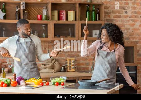 Drôle de couple marié combats avec des ustensiles de cuisine dans des outils Banque D'Images