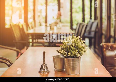 Une petite cloche pour appeler le serveur et fleurs artificielles dans une casserole en aluminium placé sur une table dans un café. Banque D'Images