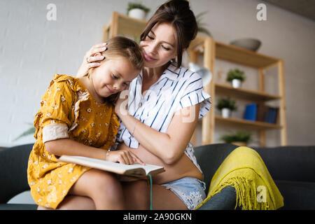 Portrait de femme enceinte et sa fille lire un livre dans le salon Banque D'Images