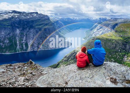 Couple siège au rock et regarde montagnes près de Trolltunga. Attraction touristique populaire. - Lac Ringedalsvatnet dans la municipalité de Odda dans Hordalan Banque D'Images