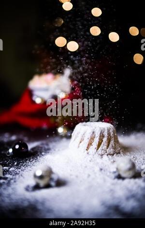 Noël au chaud à la maison avec un sweet mini gâteau bundt, le sucre en poudre sur une mini hot chaud Gâteau bundt avec ornement de Noël et une tasse de flou artistique Banque D'Images