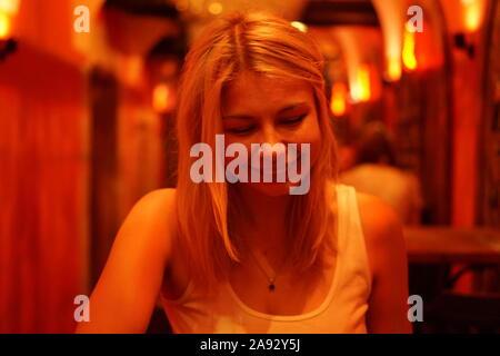 Close up portrait of smiling woman in bar ou café avec éclairage au néon