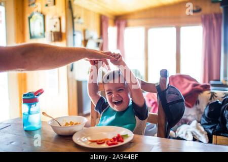 Père atteindre pour chatouiller son fils alors qu'à la table
