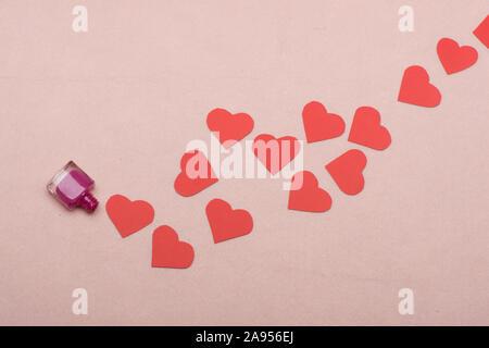 Symbole de l'amour lumière sur fond rose. Valentines Day et concept de beauté. Bouteille de vernis à ongles rose laissés ouverts, Close up. Beaucoup de chemin de faire des coeurs en papier. Banque D'Images