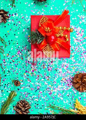 Boîte cadeau rouge avec décoration rouge sur fond bleu turquoise avec des paillettes colorées, les cônes. Maison de concept. Selective focus Banque D'Images