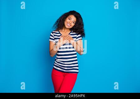 Portrait of smiling afro American girl mettre les mains paumes sur la poitrine se sentir content reconnaissant à porter des t-shirt à rayures costume trendy élégant Banque D'Images