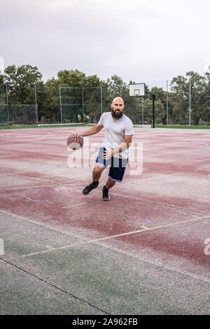 Joueur de basket-ball jeunes exécutant avec la balle sur un vieux terrain de basket-ball Banque D'Images