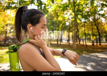 Heureux femme athlétique avec une bouteille d'eau à l'aide de smart watch en parc. copy space