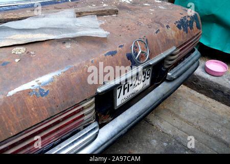 Emblème Mercedes 3 points Star monté sur le coffre arrière sur la rue : voiture classique Mercedes abandonnée, Bangkok, Thaïlande Banque D'Images