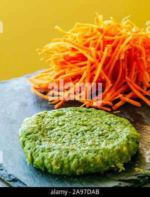 Les épinards hamburgeur avec carottes servi sur une plaque à fond jaune. Banque D'Images