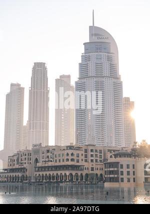 Soleil levant derrière les immeubles de grande hauteur à proximité du centre commercial de Dubaï, au centre-ville de Dubaï.