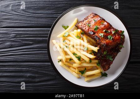 Sticky côtes courtes avec frites gros plan sur une assiette sur la table. Haut horizontale Vue de dessus Banque D'Images