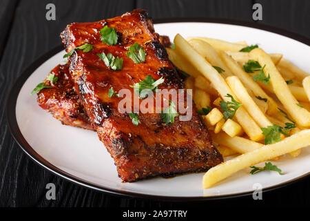 Sticky côtes courtes avec frites close-up sur une plaque sur la table horizontale. Banque D'Images