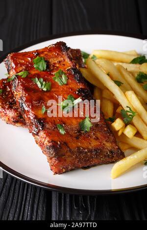 Délicieux barbecue épicée côtes courtes avec frites gros plan sur une plaque verticale sur la table. Banque D'Images