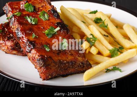 Bouts de côtes barbecue servant de frites sur une assiette sur la table horizontale. Banque D'Images
