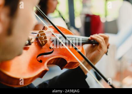 Vue arrière d'un violoniste effectuant un morceau avec son violon, l'arrière-plan flou Banque D'Images
