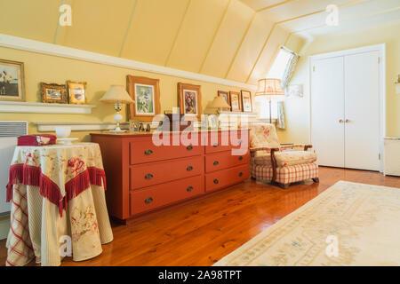 Commode en bois teinté rouge et fauteuil rembourré, tapis couleur crème, vitraux et plancher en pin huilé dans chambre des maîtres de maison ancienne. Banque D'Images