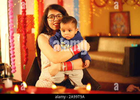 Portrait d'une belle jeune femme indienne en vêtements traditionnels tenant un bébé garçon aiguë au sein de l'arrière-plan décoratif à l'occasion de Diwali. Banque D'Images