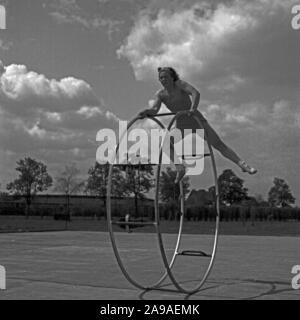 Une jeune femme exerçant avec elle gymwheel sur un terrain de sport, de l'Allemagne des années 1930.