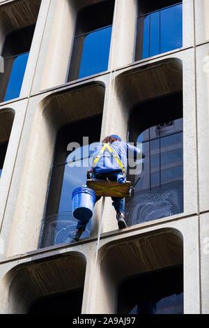 Nettoyant pour vitres sur un gratte-ciel, suspendu par une corde. Sacramento, Californie, États-Unis d'Amérique. USA Banque D'Images